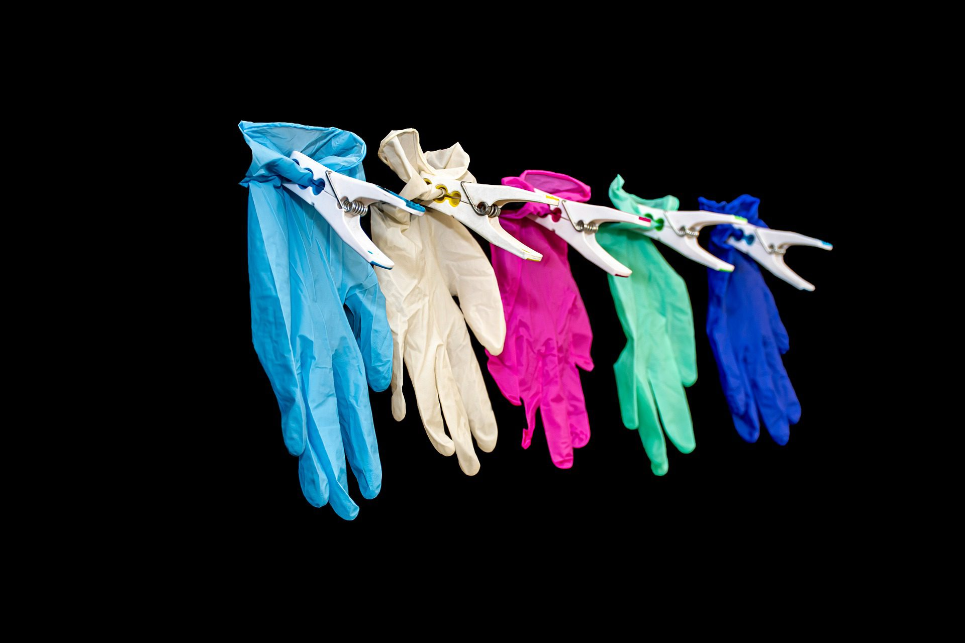 Colourful gloves pegged in a line on a black background